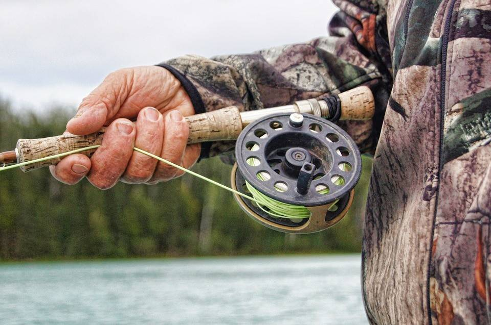 Close-up of man's hand holding fishing rod.